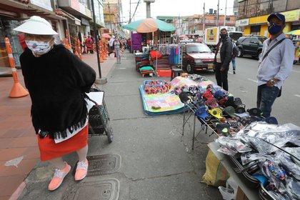 Una mujer camina frente a un vendedor informal de mascarillas en una calle de Bogotá. (Colombia). EFE/ Carlos Ortega/Archivo