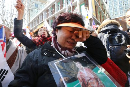 Thousands of South Koreans react after the impeachment of South Korean President Park Geun-hye before the Seoul Constitutional Court