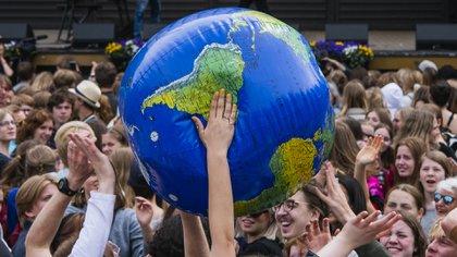 """Los manifestantes lanzan un globo de la Tierra durante la manifestación """"Huelga Global por el Futuro"""" en Estocolmo el 24 de mayo de 2019, un día mundial de protestas estudiantiles con el objetivo de incitar a los líderes mundiales a actuar sobre el cambio climático. (AFP)"""