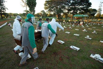 Trabajadores del cementerio Campo de Esperanza entierran una víctima de COVID-19 este jueves, en Brasilia, Brasil. La OMS afirma que Sudamérica se está convirtiendo en nuevo epicentro de la pandemia (EFE/ Joédson Alves)