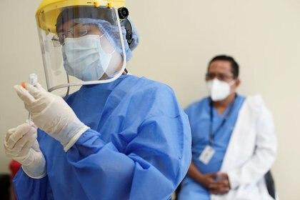 Una trabajadora de salud se prepara para administrar una dosis de la vacuna contra el COVID-19 desarrollada por Pfizer y BioNTech en un hospital de Guayaquil, Ecuador. Enero 21, 2021. REUTERS/Santiago Arcos
