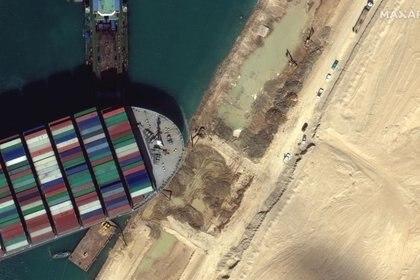 Una vista del equipo de movimiento de tierra que excava arena cerca de la proa del barco de contenedores Ever Given, (©2021 Maxar Technologies vía REUTERS)