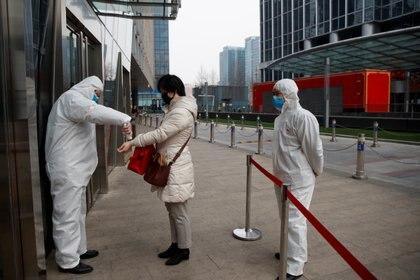 Un trabajador comprueba la temperatura de una mujer al entrar a un edificio de oficinas en el Distrito Central de Negocios de Beijing el 24 de febrero de 2020, mientras el país se ve afectado por un brote del novedoso coronavirus (REUTERS/Thomas Peter)
