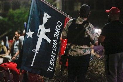 Un miembro del Florist Boys Movement sostiene una bandera frente a la Mesa del Condado de Marigopa y el Centro Electoral (MCDEC) en Phoenix, Arizona, EE. UU., El 5 de noviembre de 2020, mientras participa en una pelea por los primeros resultados de las elecciones presidenciales de 2020.  REUTERS / Jim Urgard