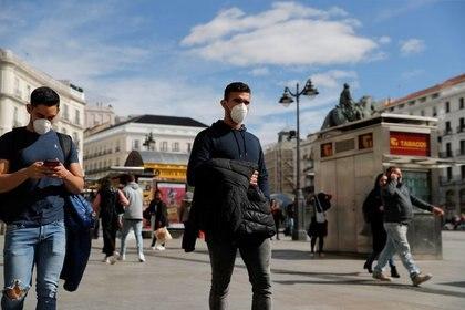 FOTO DE ARCHIVO. Hombres con mascarilla caminan por la Puerta del Sol, en Madrid, España. 4 de marzo de 2020. REUTERS/Susana Vera.
