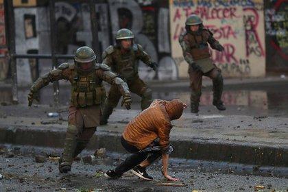 Un policía persigue a un manifestante en Santiago. REUTERS/Ricardo Moraes     TPX IMAGES OF THE DAY