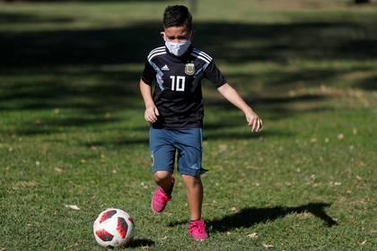 Un niño juega fútbol en un parque de Buenos Aires en medio de la pandemia del coronavirus