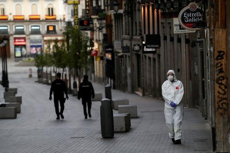 Un trabajador médico con traje protector pasa junto a dos policías en una calle vacía de Madrid, España. 22 marzo 2020. REUTERS/Susana Vera