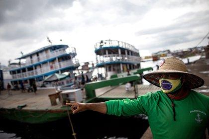 Un hombre con tapabocas de diseño de la bandera brasileña señala hacia el río Amazonas en Manaos (EFE/ Raphael Alves)