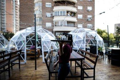 Una mujer camina con una bandeja en un restaurante equipado con domos para el aislamiento de sus clientes en la localidad de San Miguel, en la provincia de Buenos Aires (Argentina). EFE/ Juan Ignacio Roncoroni/Archivo