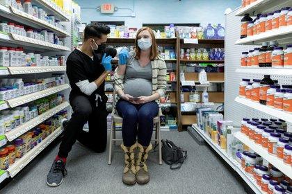 Michelle Melton, quien tiene 35 semanas de embarazo, recibe la vacuna Pfizer-BioNTech contra la COVID-19 en Skippack Pharmacy en Schwenksville, Pensilvania, Estados Unidos (Reuters)