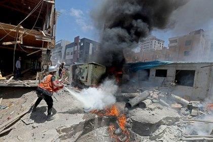 Un bombero palestino apaga un incendio en el lugar de los ataques israelíes en la ciudad de Gaza, 17 de mayo de 2021. REUTERS/Mohammed Salem