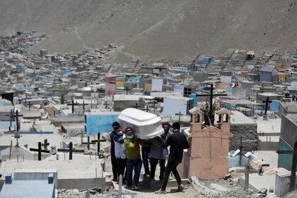 Miembros de la familia llevan el ataúd de un hombre que murió de la enfermedad del coronavirus (COVID-19) en un cementerio, en Lima, Perú (Reuters)