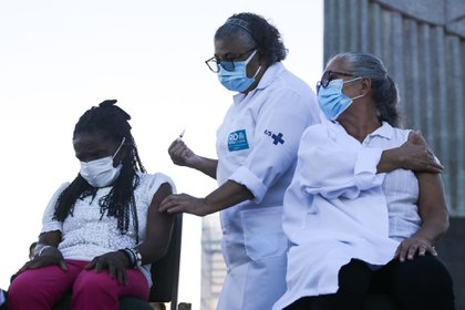 A healthcare worker administers doses of the Sinovac Biotech Ltd. coronavirus vaccine at the Christ the Redeemer statue in Rio de Janeiro, Brazil, on Monday, Jan. 18, 2021. Brazil accelerated plans to vaccinate its population against the coronavirus after an early start by the state of Sao Paulo added pressure on President Jair Bolsonaro to move faster to stem an incipient loss of popularity.