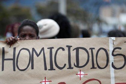 Fotografía de archivo del 28 de agosto de 2020 de una mujer que sostiene una pancarta de protesta durante una manifestación contra las masacres, en Bogotá (Colombia). EFE/ Carlos Ortega/Archivo