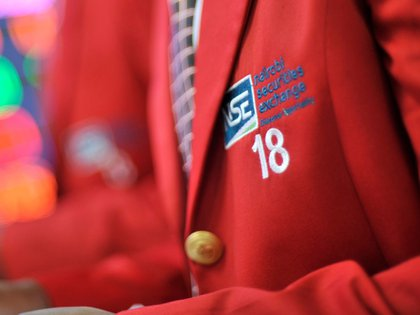 An embroidered NSE logo sits on the red jacket of an employee inside the Nairobi Securities Exchange Ltd. (NSE), in Nairobi, Kenya, on Tuesday, Dec. 8, 2015. The government had planned to plug the 2016-17 fiscal deficit with about 240 billion shillings of external borrowing, and about the same amount raised on the domestic debt market. Photographer: Bloomberg/Bloomberg
