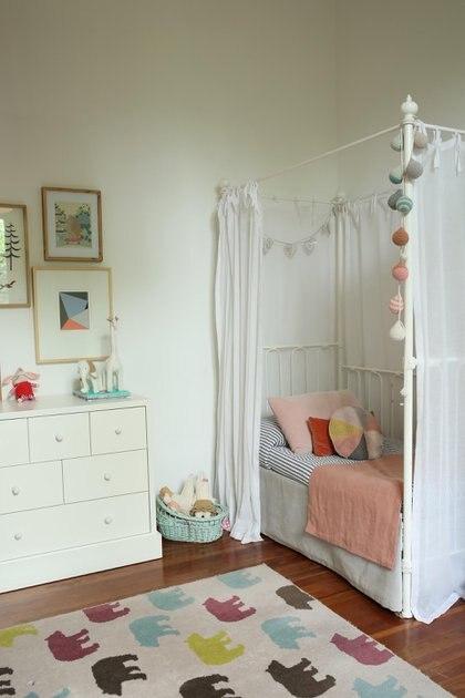 En el rincón de la foto aparece una cama de hierro con baldaquino, con cortinas de gasa de algodón haciendo juego con la ropa de cama y almohadones.