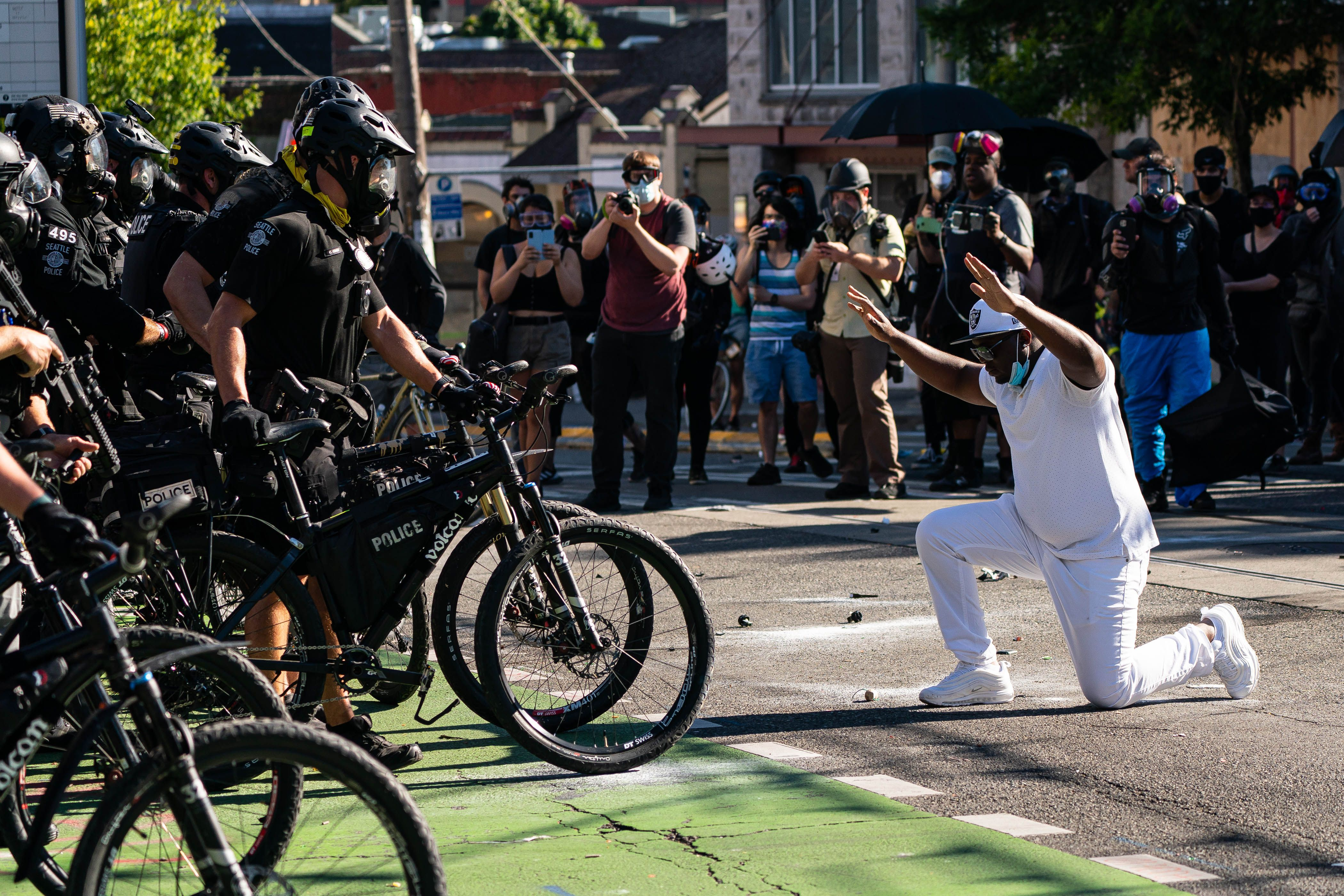 SEATTLE, WA - JULY 25: A demonstrator kneels in front of police during protests in Seattle on July 25, 2020 in Seattle, Washington. Police and demonstrators clash as protests continue in the city following reports that federal agents may have been sent to the city.   David Ryder/Getty Images/AFP