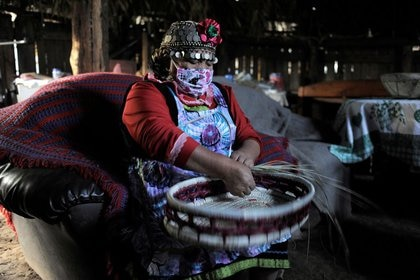 Estela Astorga Porma, una mujer mapuche, usa una mascarilla mientras teje una canasta dentro de su 'Ruka' (Casa) para venderla en una feria nativa, en medio de la propagación de la enfermedad por coronavirus (COVID-19) en el área de Huentelolén cerca del pueblo de Tirúa, en el sur de Chile, 7 de mayo de 2020. REUTERS / José Luis Saavedra