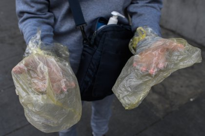 A man covers his hands with plastic bags as a preventive measure against the spread of the new coronavirus, COVID-19, in Caracas, on March 20, 2020. (Photo by Federico PARRA / AFP)