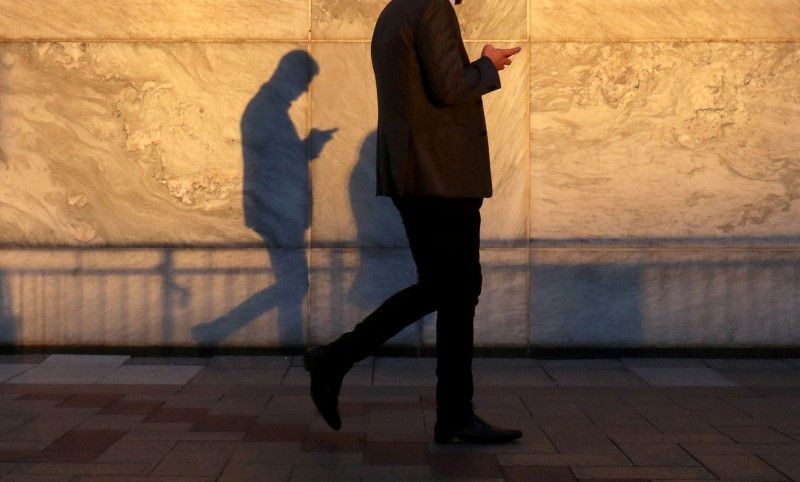 FILE PHOTO: An unidentified man using a smart phone walks through London's Canary Wharf financial district in the evening light in London, Britain, September 28, 2018.   REUTERS/Russell Boyce/File Photo