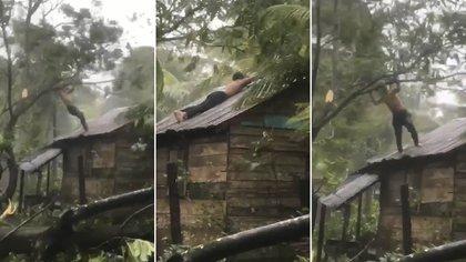 Byron Nihimaya Cirilo de 32 años, se aferra con todas sus fuerzas del techo de su casa mientras intenta que no se vuele por efecto de los fuertes vientos del huracán Eta.