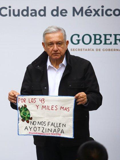 El presidente de México, Andrés Manuel López Obrador, sostiene una pieza de tela bordada por un familiar de uno de los 43 estudiantes desaparecidos de la Escuela Normal Rural de Ayotzinapa, mientras asisten a la entrega de un informe de investigación con motivo del sexto aniversario de su desaparición, en la Palacio en la Ciudad de México, México 26 de septiembre de 2020.