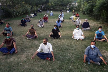 People wearing masks to help curb the spread of the coronavirus and maintaining social distancing attend a Yoga class at a park in Lahore, Pakistan, Saturday, June 20, 2020. (AP Photo/K.M. Chaudary)