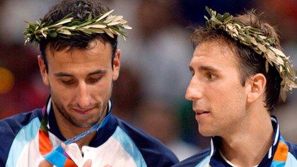 Manu Ginóbili y Pepe Sánchez observan emocionados las medallas obtenidas en los Juegos Olímpicos de Atenas. Foto: AFP PHOTO/DON EMMERT
