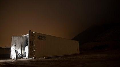 Trabajadores de un hospital trasladan el cuerpo de una supuesta víctima de coronavirus a un contenedor de mercancías refrigerado en los terrenos del hospital público Hipólito Unanue, en Lima, Perú, el 15 de mayo de 2020. (AP Foto/Rodrigo Abd)