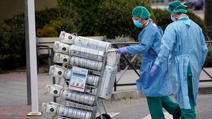 FOTO DE ARCHIVO: Trabajadores de la salud con máscaras faciales protectoras llevan tanques de oxígeno a la unidad de emergencia en el Hospital 12 de Octubre, en medio del brote de coronavirus COVID-19 (Reuters)