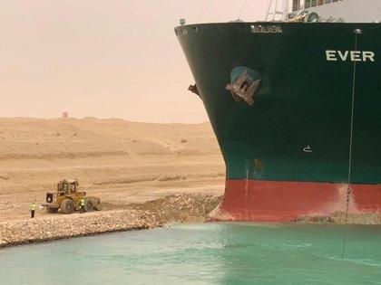Los trabajadores se ven junto al buque portacontenedores que fue golpeado por un fuerte viento y encalló en el Canal de Suez, Egipto. Suez Canal Authority/Handout via REUTERS