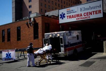 Los paramédicos llevan en silla de ruedas a un paciente desde una ambulancia hasta una zona de llegada de emergencia en el Hospital Elmhurst durante el brote de la enfermedad coronavirus (COVID-19) en el barrio de Queens de la ciudad de Nueva York, Nueva York, EE.UU., el 6 de abril de 2020. (REUTERS/Eduardo Muñoz)