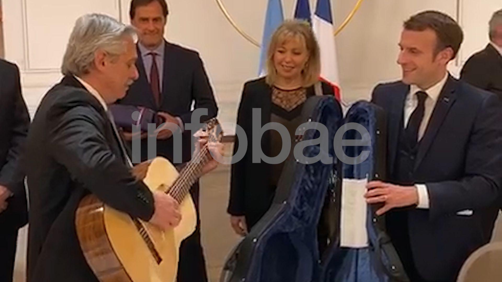 Alberto Fernández toca la guitarra que le regaló Macron durante el almuerzo que compartieron en París