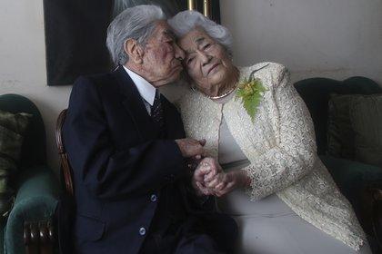 Los esposos Julio Mora Tapia, de 110 años, Waldramina Quinteros, de 104, ambos profesores retirados, posan para una foto en su hogar en Quito, Ecuador.  (AP Foto/Dolores Ochoa)