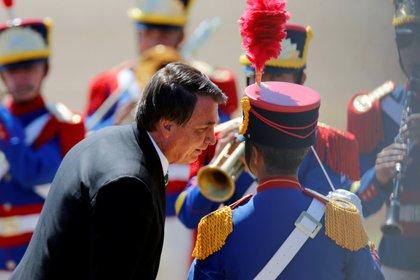 Bolsonaro dialoga con el director de la banda militar que musicalizó el acto (REUTERS/Adriano Machado)