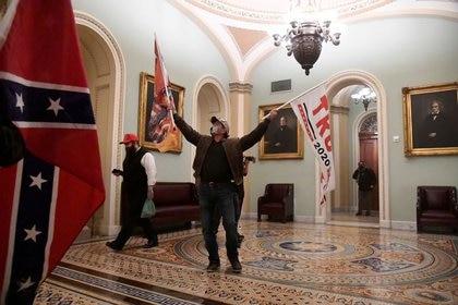 Los partidarios del presidente de Estados Unidos, Donald Trump, ondean banderas de Trump y banderas de batalla confederadas mientras se manifiestan en el segundo piso del Capitolio, cerca de la entrada del Senado después de violar las defensas de seguridad, en Washington DC, Estados Unidos. 6 de enero de 2021 (REUTERS/Mike Theiler)