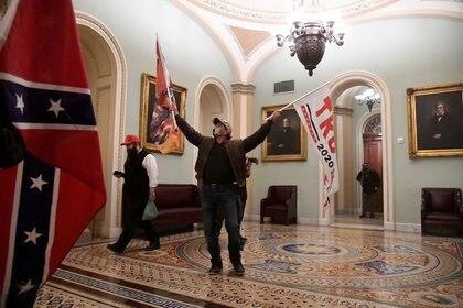 Los partidarios del presidente de Estados Unidos, Donald Trump, ondean banderas de Trump y banderas de batalla confederadas mientras se manifiestan en el segundo piso del Capitolio a comienzos de enero (REUTERS/Mike Theiler)
