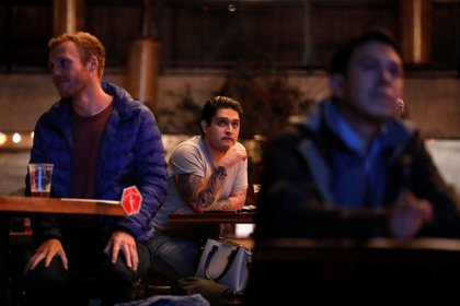Americans living in Mexico react as they watch the first 2020 presidential campaign debate between U.S. President Donald Trump and Democratic presidential nominee Joe Biden at the Pinche Gringo restaurant in Mexico City, Mexico, September 29, 2020. REUTERS/Carlos Jasso