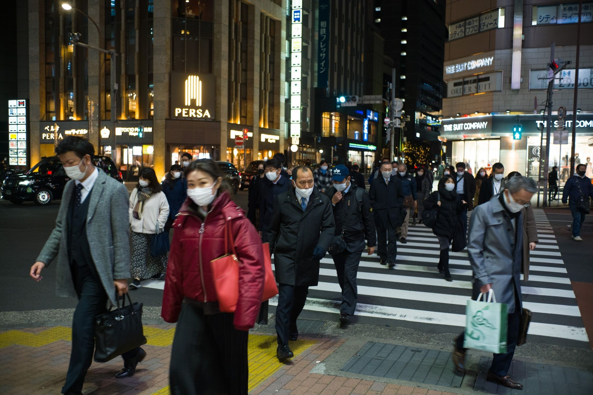 Evening commuters wearing protective masks cross a street in Tokyo, Japan, on Friday, Jan. 8, 2021. The state of emergency over the coronavirus that went into effect Friday for Tokyo and its surrounding area will weigh on Japans economy this quarter, said Japan's Finance Minister Taro Aso. Photographer: Kentaro Takahashi/Bloomberg