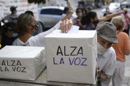 Una persona vota en Caracas en la consulta popular organizada por los partidos democráticos venezolanos en rechazo a la elección fraudulenta organizada por el régimen de Maduro (12 de diciembre)