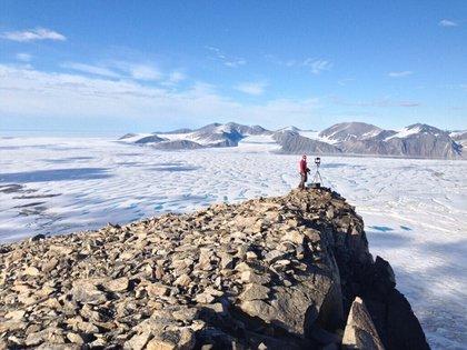 Una analista del Servicio Canadiense de Hielos tomando fotografías de grietas en la plataforma de hielo Milne, que se ha roto a finales de julio de 2020. (Luke Copland vía AP)