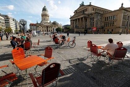 La gente disfruta del clima en un café de la plaza Gendarmenmarkt donde se aplican medidas de distanciamiento social, durante el brote de la enfermedad coronavirus (COVID-19), en Berlín, Alemania, el 16 de mayo de 2020 (REUTERS/Fabrizio Bensch)
