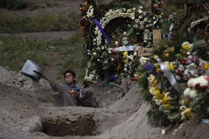 El trabajador de un cementerio cava una tumba en una sección del Cementerio Municipal de Valle de Chalco que se abrió a inicios de la pandemia de coronavirus para lidiar con el aumento de decesos, a las afueras de la Ciudad de México, el jueves 24 de septiembre de 2020.  (AP Foto/Rebecca Blackwell)