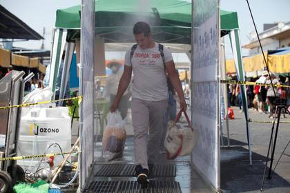 Un hombre cruza un túnel sanitario, que aplica un baño de ozono como medida preventiva ante el COVID-19, este domingo en un mercado de abastos de la ciudad de Guadalajara, en el estado de Jalisco Foto: EFE/Francisco Guasco