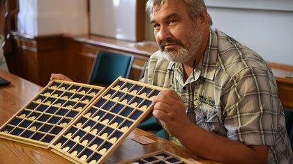El arqueólogo Milan Metlicka posa junto a las monedas (Museo de Bohemia Occidental en Pilsen / Václav Marian)