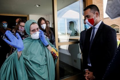Silvia Romano sonríe, tras un velo y una mascarilla para protegerse de COVID-19 en un aeropuerto militar en Roma (Reuters)