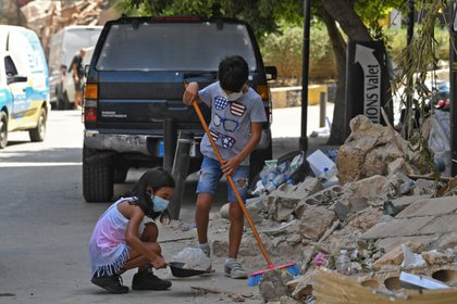 Dos niños ayudan con la limpieza de la ciudad, días despues de la terrible explosión (AFP)