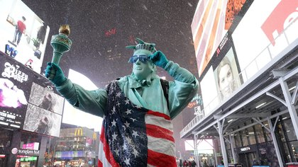 Una persona vestida con un disfraz de la Estatua de la Libertad y envuelta en una bandera de EE. UU. bajo la nieve en Times Square  (Foto de TIMOTHY A. CLARY / AFP)