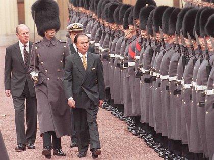 Tras asumir la presidencia, Menem restableció las relaciones diplomáticas con Gran Bretaña, interrumpidas tras la Guerra de Malvinas. En 1998 viajó en visita oficial de seis días a Gran Bretaña, tras 38 años de ausencia de un mandatario argentino en el Reino Unido. Aquí junto al duque de Edinburgo, Felipe, recibido por la Guardia de Honor del Palacio de Buckingham, donde tomó el te con la reina Isabel junto a su hija Zulemita. Esa fue la última vez que la monarca recibió a un mandatario argentino.